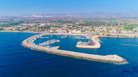 Aerial birds eye view of Zygi fishing village port, Larnaca, Cyprus. The fish boats moored in the harbour with docked yachts and skyline of the town near Limassol from above. Stock Photo