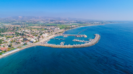 Aerial birds eye view of Zygi fishing village port, Larnaca, Cyprus. The fish boats moored in the harbour with docked yachts and skyline of the town near Limassol from above. Banco de Imagens