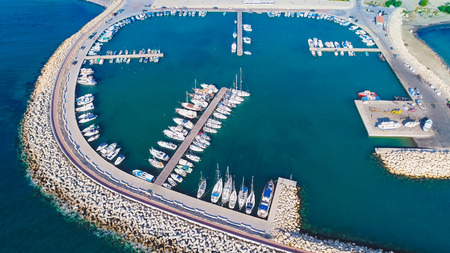 Aerial birds eye view of Zygi fishing village port, Larnaca, Cyprus. The fish boats moored in the harbour with docked yachts and skyline of the town near Limassol from above. Editorial