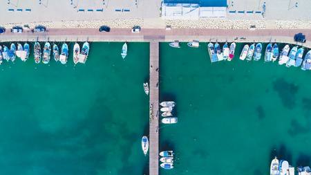 Aerial birds eye view of Zygi fishing village port, Larnaca, Cyprus. Bird eye view of aligned fish boats moored in the harbour, docked yachts, pier, wave breaker rocks near Limassol from above.