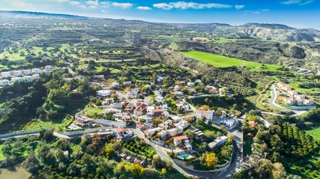 Aerial birds eye view of Goudi village in Polis Chrysochous valley, Paphos, Cyprus. View of traditional ceramic tile roof houses, church, trees, hills and Akamas - Latchi beach bay from above.