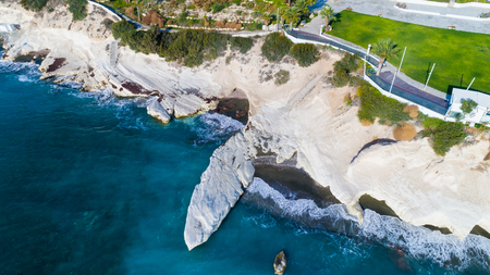 Aerial view of landmark big white chalk rock at Governors beach, Limassol, Cyprus. The steep stone cliffs and deep blue sea waves crushing in coves and dark sand next to Kalymnos fish restaurant from above.