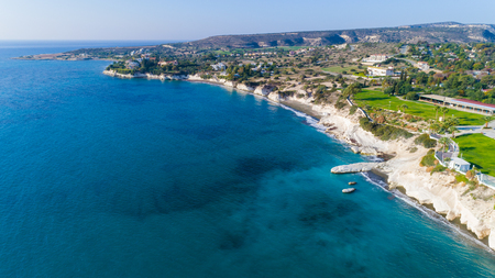 Aerial view of coastline and landmark big white chalk rock at Governors beach, Limassol, Cyprus. The steep stone cliffs and deep blue sea waves crushing in coves and dark sand next to Kalymnos fish restaurant from above. Banco de Imagens