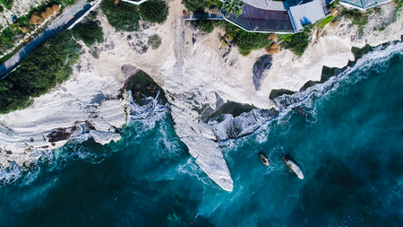 Aerial view of landmark big white chalk rock at Governors beach, Limassol, Cyprus. The steep stone cliffs and deep blue sea waves crushing in coves and dark sand from above. Banco de Imagens