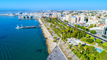 Aerial view of Molos Promenade park on the coast of Limassol city centre in Cyprus. Birds eye view of the jetties, beachfront walk path, palm trees, Mediterranean sea, piers, rocks, urban skyline and port from above. Banco de Imagens