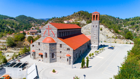 Aerial view of Agios Arsenios church, Kyperounda village, Limassol, Cyprus. Traditional landmark christian greek orthodox, ceramic tiled roof, stone bell tower architecture in Kyperounta from above