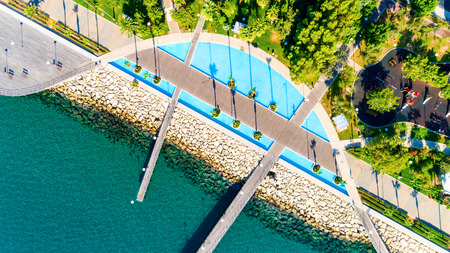 Aerial view of Molos Promenade park on the coast of Limassol city centre in Cyprus. Birds eye view of the jetties, beachfront walk path, palm trees, Mediterranean sea, piers, rocks, urban skyline and port from above. Editorial