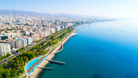 Aerial view of Molos Promenade park on the coast of Limassol city centre in Cyprus. Bird's eye view of the jetties, beachfront walk path, palm trees, Mediterranean sea, piers, rocks, urban skyline and port from above.