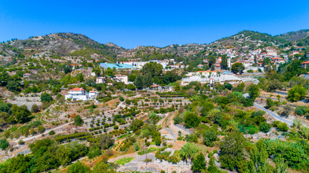 Aerial view of Agros village settlement on mountain Troodos, Limassol district, Cyprus. Birds eye view of traditional houses with ceramic tile roof, church, countryside and rural landscape from above.