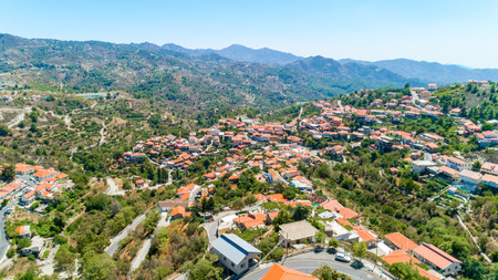 Aerial view of Kyperounda village on Madari, Troodos mountain, Limassol, Cyprus. Bird eye view of traditional ceramic tiled roof houses, countryside, valley and church from above. Banco de Imagens