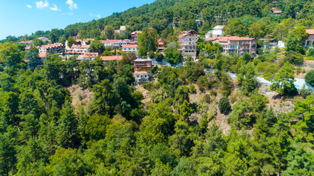 Aerial view of Pano Platres village,winter resort, on Troodos mountains, Limassol, Cyprus. Birds eye view of pine tree forest, red roof tiled houses, hotels, panagias faneromenis church from above.