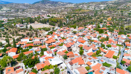 Aerial Lania (Laneia) wine village, Limassol, Cyprus. Birds eye view of traditional Mediterranean, picturesque alleys, red ceramic roof tile houses, vineyards, church and entrance. Banco de Imagens