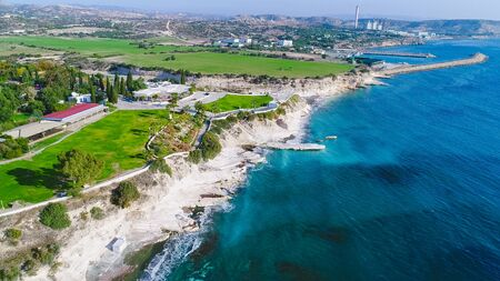 Aerial view of coastline and landmark big white chalk rock at Governor's beach, Limassol, Cyprus. The steep stone cliffs and deep blue sea waves crushing in coves and dark sand next to Kalymnos fish restaurant from above and vasilikos power station in the background.