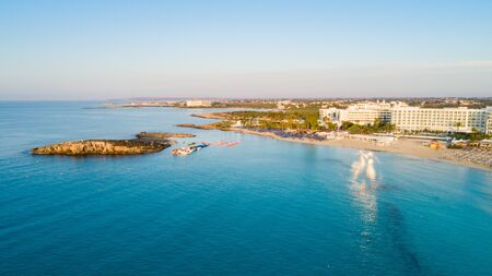 Aerial bird's eye view of famous Nissi beach coastline, Ayia Napa, Famagusta, Cyprus. The landmark tourist attraction islet bay at sunrise with golden sand, sunbeds, sea restaurants in Agia Napa on summer holidays, from above.