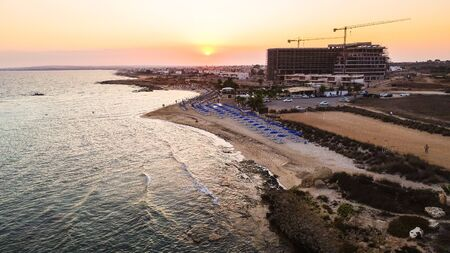 Aerial view of coastline sunset and landmark beach of Agia Thekla, Ayia Napa, Famagusta, Cyprus from above. Bird's eye skyline view of tourist attraction golden sand bay, islet, sunbeds in Ammochostos. 写真素材
