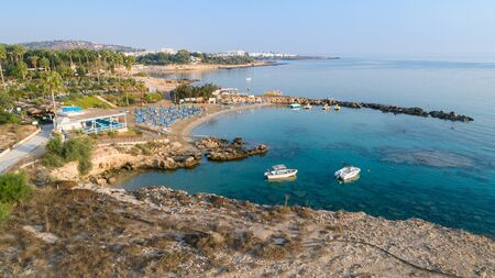 Aerial bird's eye view of Green bay in Protaras, Paralimni, Famagusta, Cyprus. The famous tourist attraction diving location rocky beach with boats, sunbeds, restaurants, water sports, people swimming in sea on summer holidays, from above.