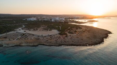 Aerial bird's eye view of Landa beach, Ayia Napa, Famagusta, Cyprus. The landmark tourist attraction golden sand bay at sunrise with sunbeds, sea restaurants between Makronissos and nissi in Agia Napa on summer holidays, from above. 写真素材