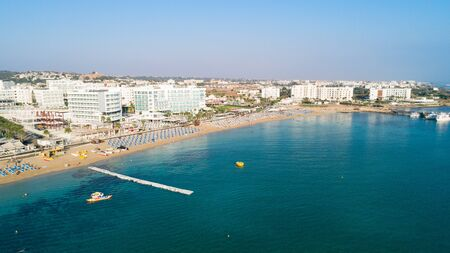 Aerial bird's eye view of Sunrise beach at Fig tree in Protaras, Paralimni, Famagusta, Cyprus. The famous tourist attraction family bay with golden sand, boats, sunbeds, restaurants, water sports, people swimming in sea on summer holidays, from above. 写真素材