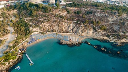 Aerial bird's eye view of Konnos beach in Cavo Greco Protaras, Paralimni, Famagusta, Cyprus. The famous tourist attraction golden sandy Konos bay with boats, yachts, sunbeds, water sports, people swimming in sea on summer holidays, from above.