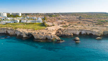 Aerial view of coastline and landmark Love bridge, international sculpture park and sea caves, at Cavo Greco, Ayia Napa, Famagusta, Cyprus from above. Bird's eye view of tourist attraction cliff rock natural formation rocky arch in Ammochostos from above. Editorial