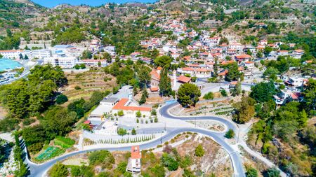 Aerial view of Agros village settlement on mountain Troodos, Limassol district, Cyprus. Bird's eye view of traditional houses with ceramic tile roof, church, countryside and rural landscape from above.