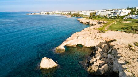 Aerial view of coastline and landmark Love bridge and sea caves, at Cavo Greco, Ayia Napa, Famagusta, Cyprus from above. Bird's eye view of tourist attraction cliff rock natural formation rocky arch in Ammochostos from above.