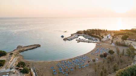 Aerial view of coastline sunset and landmark white washed chapel at Agia Triada beach, Protaras, Famagusta, Cyprus from above. Bird's eye view of tourist attraction Ayia Trias bay church, sand, sun beds at sunrise in Ammochostos district. Banco de Imagens