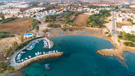 Aerial view of coastline sunset and landmark white washed chapel at Agia Triada beach, Protaras, Famagusta, Cyprus from above. Bird's eye view of tourist attraction Ayia Trias bay church, sand, port at sunrise in Ammochostos district.