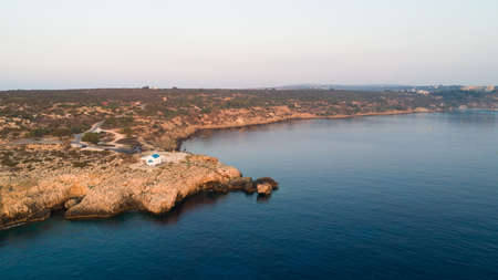 Aerial view of coastline sunset and landmark white washed chapel Agioi Anargyroi, at Cavo Greco Protaras, Famagusta, Cyprus from above. Bird's eye view of tourist attraction cliff rock Ayioi Anargiroi church, caves, beach at sunrise in Ammochostos district.
