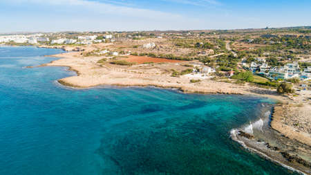 Aerial bird's eye view of Ammos tou Kambouri beach, Ayia Napa, Cavo Greco, Famagusta, Cyprus. The landmark tourist attraction rocky beach with golden sand, sunbeds,sea restaurant in Agia Napa on summer holidays, from above.
