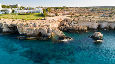 Aerial view of coastline and landmark Love bridge, international sculpture park and sea caves, at Cavo Greco, Ayia Napa, Famagusta, Cyprus from above. Bird's eye view of tourist attraction cliff rock natural formation rocky arch in Ammochostos from above. Banco de Imagens