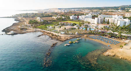 Aerial bird's eye view of Pernera beach in Protaras, Paralimni, Famagusta, Cyprus. The famous tourist attraction golden sandy bay with sunbeds, water sports, hotels, restaurants, people swimming in sea on summer holidays from above. Banco de Imagens