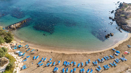 Aerial bird's eye view of Sirena beach in Protaras, Paralimni, Famagusta, Cyprus. The famous Sirina bay tourist attraction with sunbeds, golden sand, restaurant, people swimming in sea on summer holidays from above.