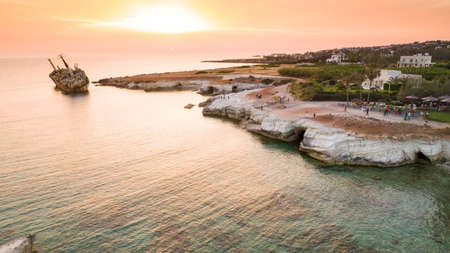 Aerial bird's eye view of the abandoned ship wreck EDRO III in Pegeia, Paphos, Cyprus from above at sunset. The rusty shipwreck stranded on Peyia rocks at sea caves near Coral Bay in Pafos, standing on coast.