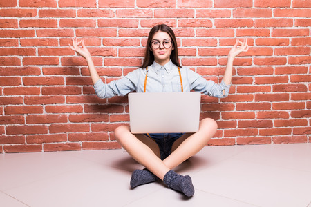 sholders: Beautiful young dark-haired girl in casual clothes posing with laptop on sholders, hands up, sitting cross-legged against brick wall Stock Photo