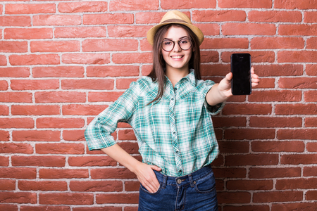 demonstrate: Beautiful young dark-haired girl in casual clothes, hat and eyeglasses posing, smiling and demonstrate on smartphone, standing against brick wall
