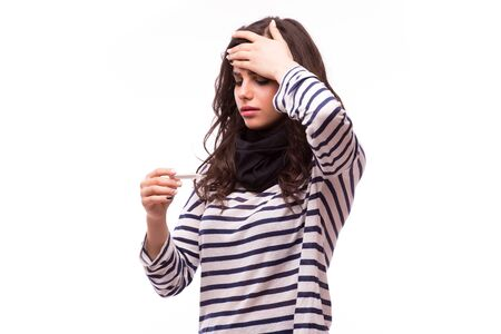 colds: Young sick woman in scarf and home clothes looking at thermometer. Sick girl with a thermometer on a white background, isolate, flu, colds Stock Photo