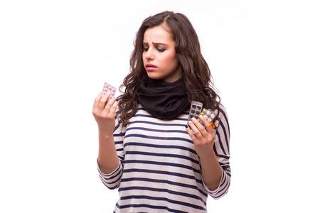 contagious: Sad young woman having flu takes pills on white background. Stock Photo