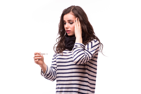 colds: Young sick woman in scarf and home clothes shock looking at thermometer. Sick girl with a thermometer on a white background, isolate, flu, colds