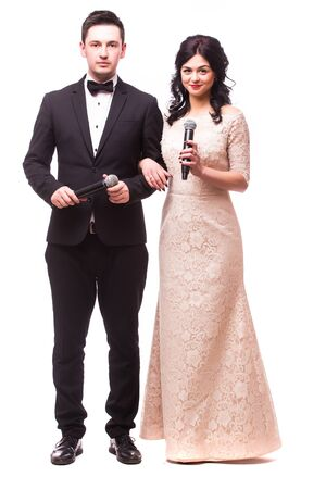 the showman: The Showman and showwoman. Young elegant man  and woman holding microphone against white background. Showman concept. Stock Photo