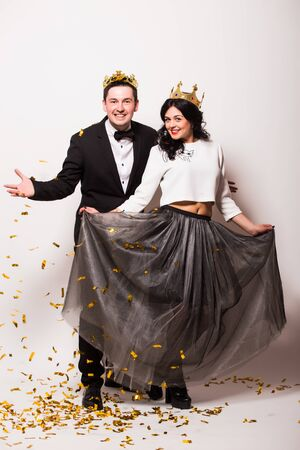 the showman: Young elegant man  and woman with crown against white background. Showman concept. Stock Photo