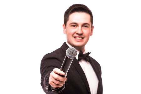 showman: The Showman  interviewer. Young elegant man holding microphone against white background.Showman concept.