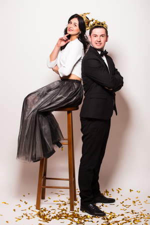 showman: Young elegant man  and woman sitting on chair with crown against white background. Showman concept.