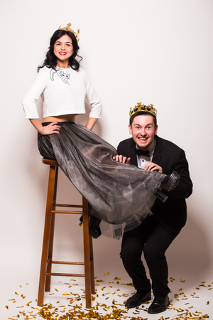 showman: Young elegant man and woman  sitting on chair  with crown against white background. Showman concept. Stock Photo