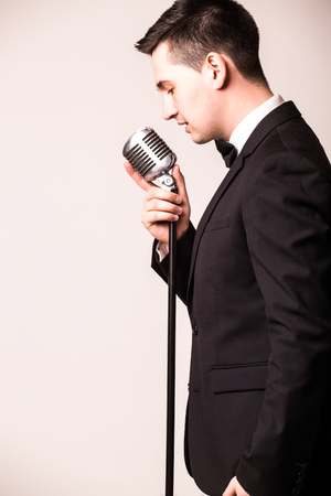 the showman: Young man in suit singing over the microphone with energy. Isolated on white background. Singer concept. Stock Photo
