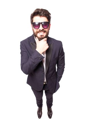 full height: Full height Confident young handsome man in sunglasses hand on chin and looking at camera while standing against white background.