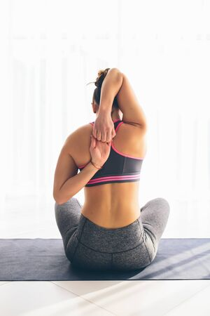 ardha: Gomukhasana. Beautiful yoga woman practice in a traning hall background. Yoga concept. Stock Photo