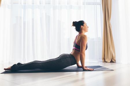 ushtrasana: Beautiful yoga woman practice in a traning hall background. Yoga concept.