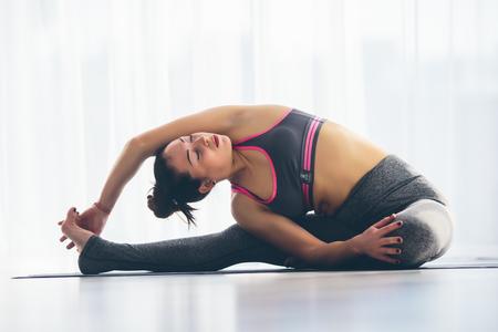 ardha: Djanu-shirasana. Beautiful yoga woman practice in a traning hall background. Yoga concept.