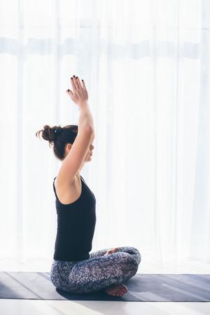 sukhasana: Sukhasana. Beautiful yoga woman practice in a traning hall background. Yoga concept.